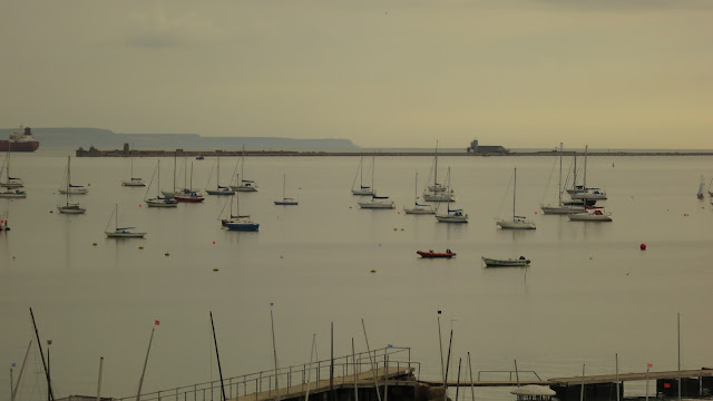 Boats mored on still water in Portland Harbour, Dorset, England
