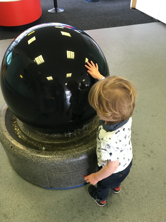 toddler-with-hand-on-massive-stone-ball-on-water-feature