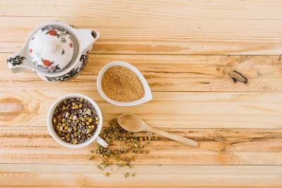 Azúcar y tetera cerca de té de manzanilla