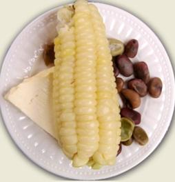 Foto de un plato con choclo y acompañantes