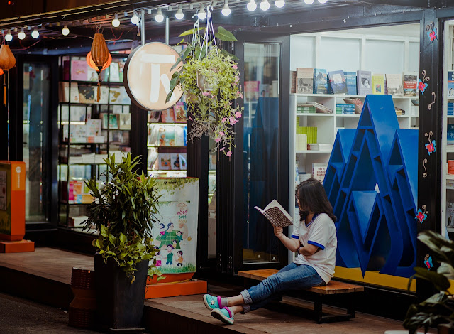 Young woman outside of shop, sitting on bench reading, book
