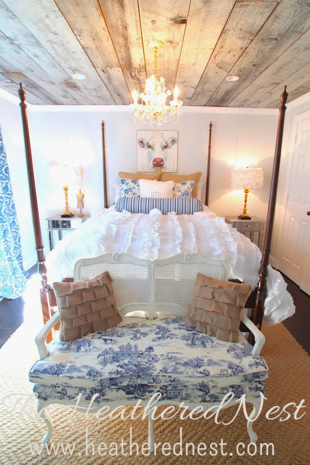 heathered nest guest room, heathered nest be our guest, be our guest, heathered nest cow, toile, burlap, barnboard ceiling, ruffle duvet, toile settee, poster bed, blue and white decor, flower lampshades