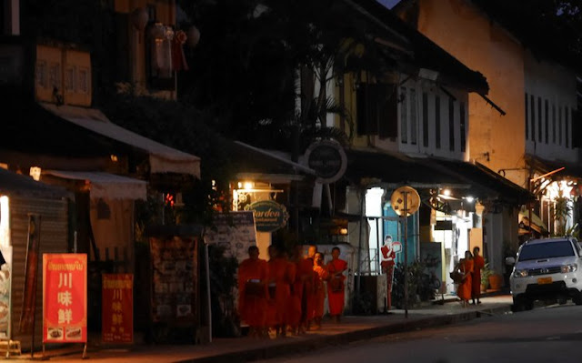 monks walking in a line through Luang Prabang before sunrise
