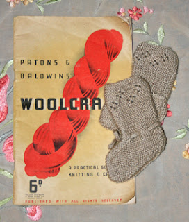 A copy of Patons woolcraft dating from the 1930s with two knitted baby bootees on top
