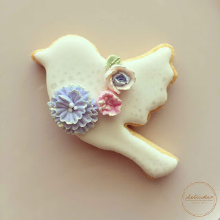 dove cookie decorated with natural food coloured piped icing flowers