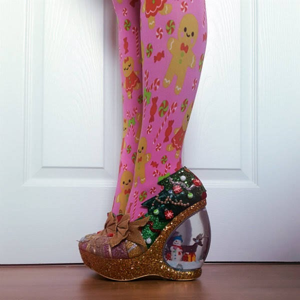 side view of legs in pink Christmas tights with glitter and velvet shoe with christmas tree detail on side and snowglobe heel