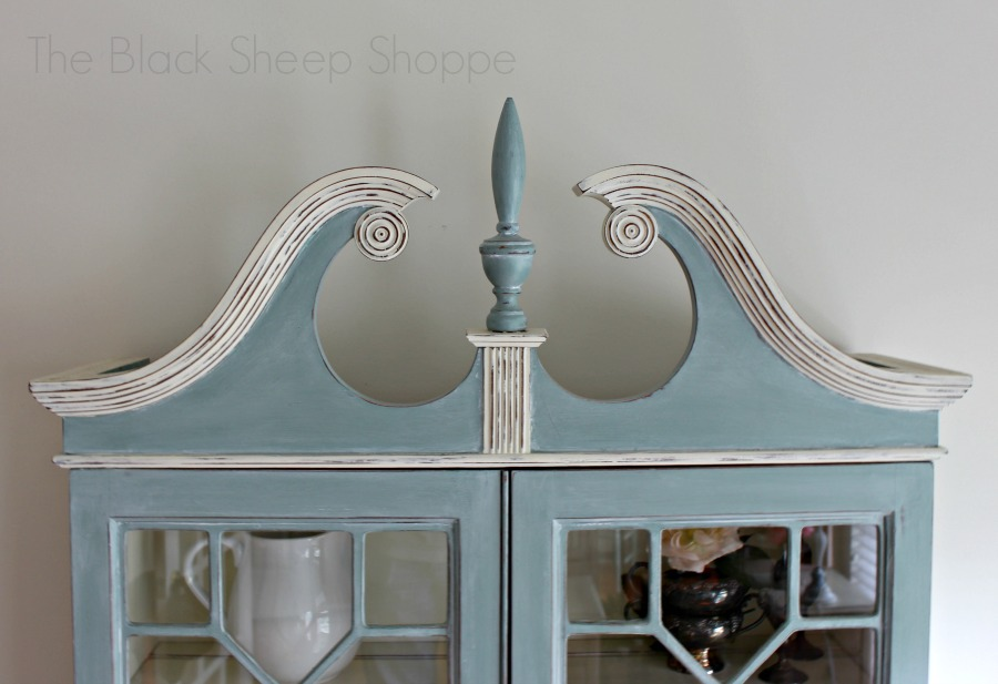 The secretary desk is topped with decorative molding and a flame finial.