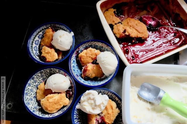preparing to serve fresh cherry and blueberry cobbler with vanilla ice cream