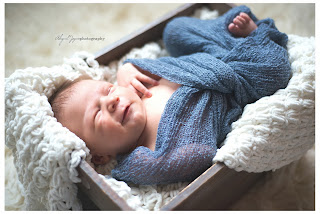 Baby photo with newborn in box wrapped with blankets smiling