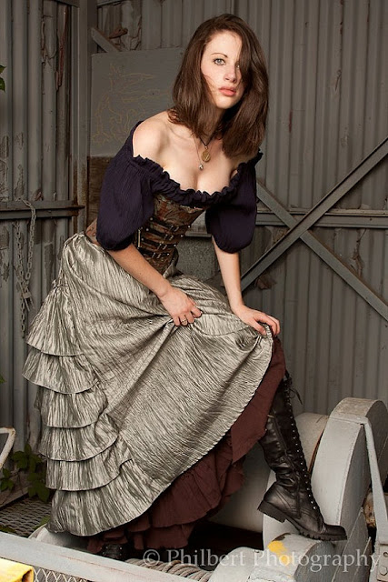 Steampunk maiden wearing a women's costume for renaissance fairs, steampunk festivals, etc. Long silver bustle skirt, purple/navy blue blouse/chemise, brown corset and black lace up boots. Steampunk female fashion inspo..