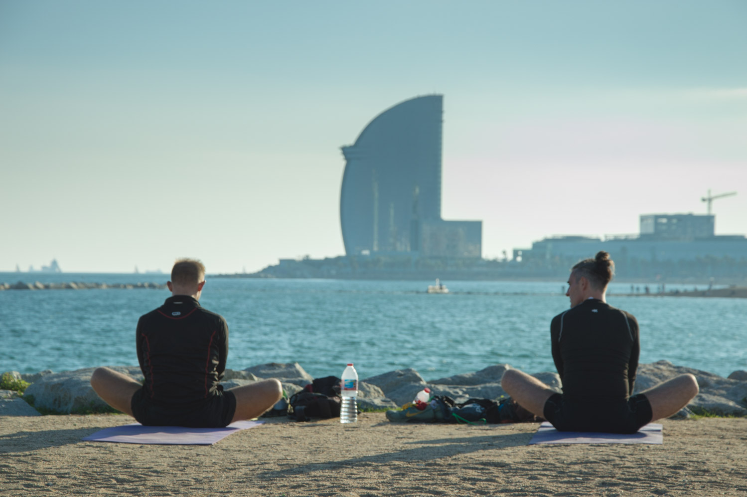 People doing yoga on the beach in Barcelona