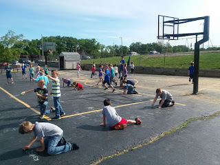 Group of students on the play ground drawing with chalk