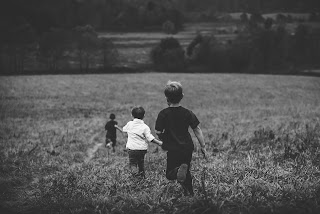 Is It OK To Leave a Child Alone? Three boys running across a field in black and white