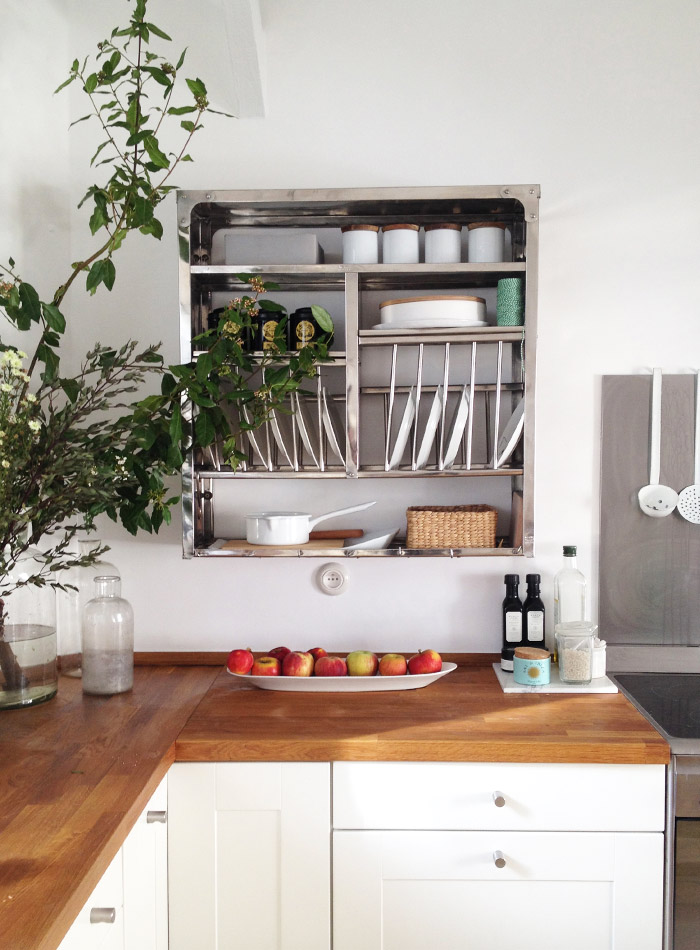 Modern farmhouse kitchen with plate rack, butcherblock counters, and white cabinets in 1650 Marais Paris home of Lucille Gauthier-Braud. #countrykitchen #modernfarmhouse #platerack