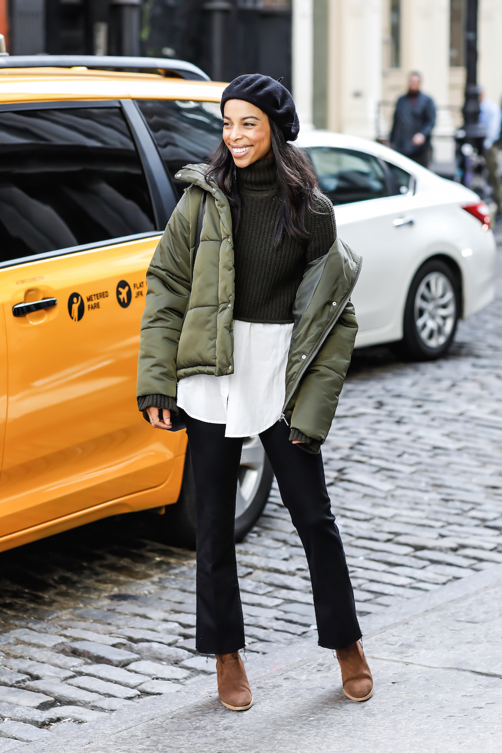 A Polished Way to Wear a Puffer Coat This Winter — Beret, Green Puffer Jacket, Flared Black Jeans, and Brown Boots