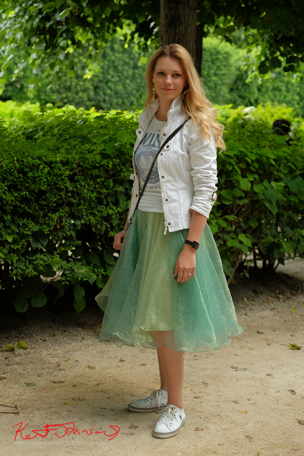 Paris Street Fashion, woman photographed at the Rodin museum wearing a wistful green silk skirt with a white tee shirt, white jean jacket and sneakers. Photographed by Kent Johnson for Street Fashion Sydney - Paris Edition.