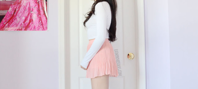 Details on the peach pink pastel pleated chiffon skirt/skort from Dresslink, paired with a long sleeve white crop top for a summer-ready outfit.