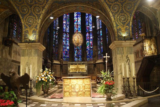 Ein goldener Altar vor dem Chor des Aachener Doms. Im Hintergrund große, bunte Kirchenfenster