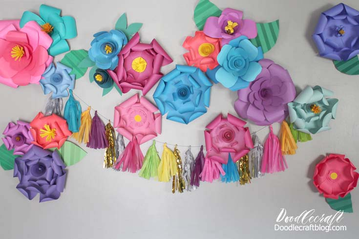 Bright colored paper flowers stuck to a wall for the perfect party backdrop.
