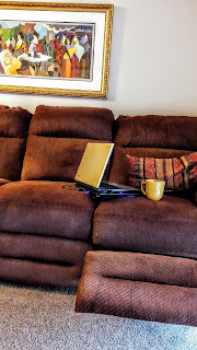 An empty couch foot rest raised with a laptop and cup sitting on the seat.
