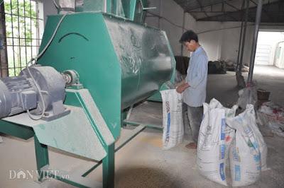 Công nhân sản xuất cám phục vụ đàn heo tại trang trại của ông Long ở huyện Thanh Oai (Hà Nội).