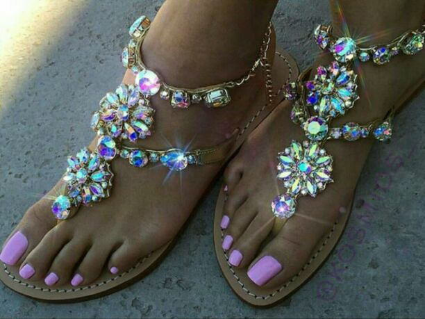 Sparkling sandals with lilac nail polish on feet