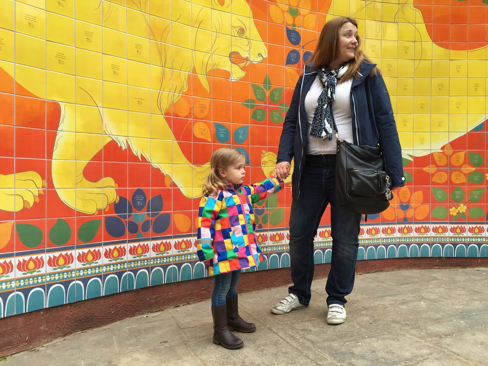 mother and daughter in front of the london zoo land of the lions yellow mural