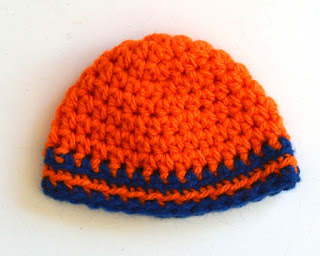 The front of the orange beanie with blue trim.