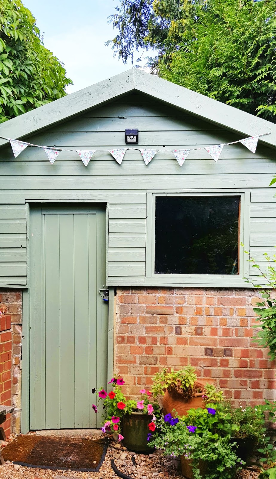 Part brickwork, part wood shed painted Cuprinol rosemary green and decorated with bunting