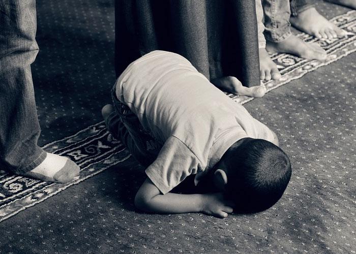 menino em jejum orando prostrado de joelhos no chao