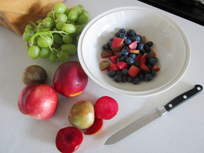 Pluots, nectarines, white nectarines and grapes are on a white kitchen counter with a knife. There is a white bowl on the same table with blueberries and some cut nectarines