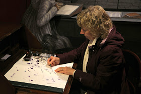 Rachel trying to write with a pen and ink at the Jane Austen Centre in Bath