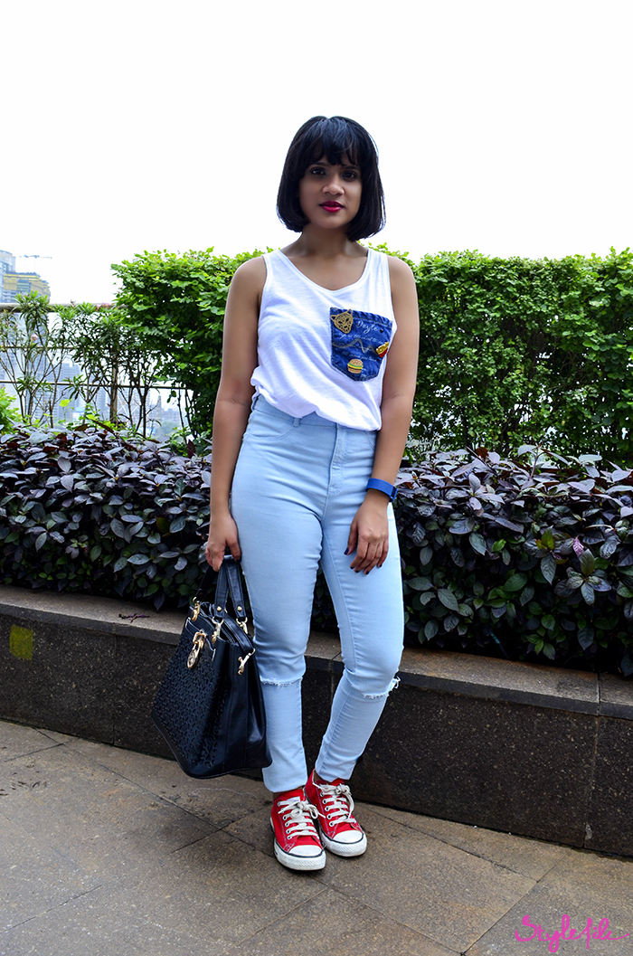 A girl shows off her street style at Lakme Fashion Week in a white tank top, high waist jeans, red sneakers, enamel pins and satchel