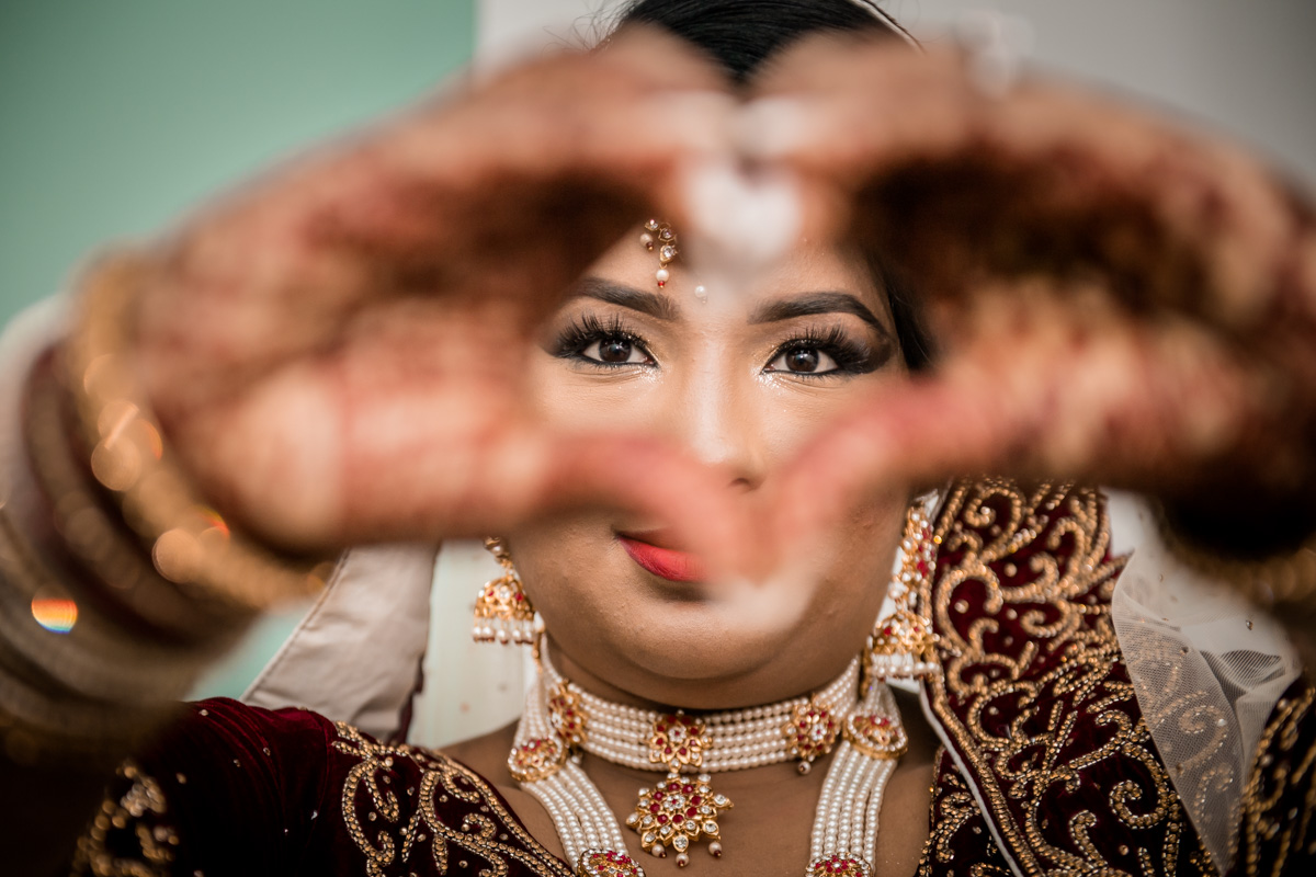 The bride making a symbol of love that unites her and her handsome man.