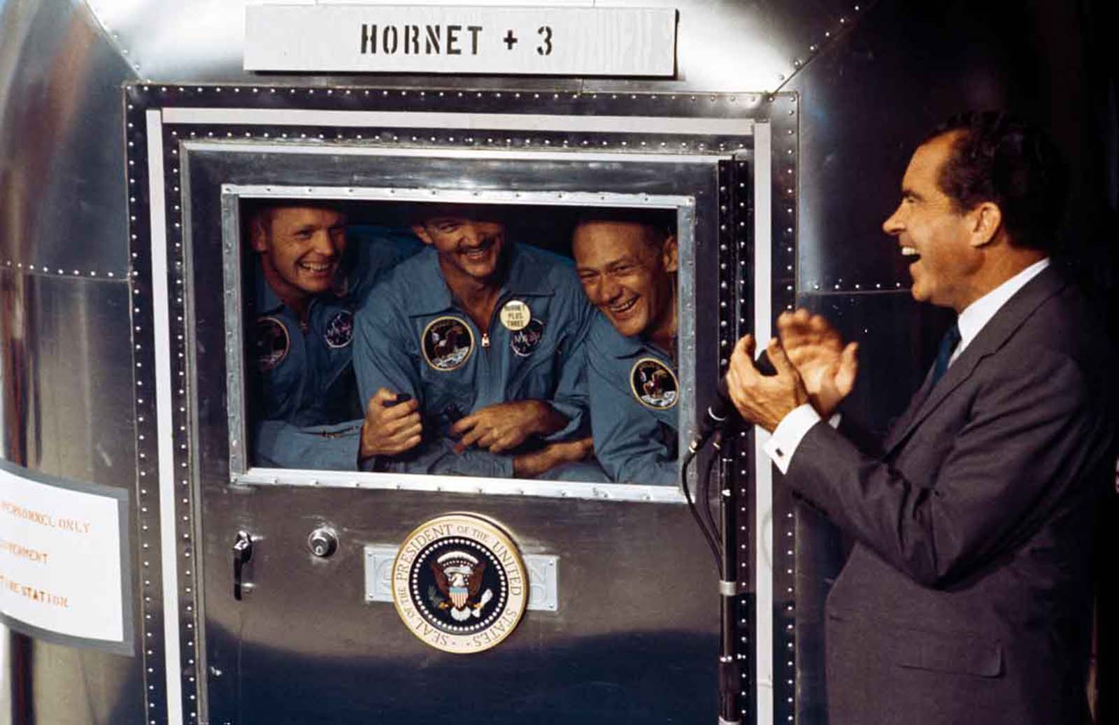 From left to right, Neil Armstrong, Michael Collins and Edwin 'Buzz' Aldrin Jnr, the crew of the historic Apollo 11 moon landing mission are subjected to a period of quarantine upon their return to earth. Through the window of their Mobile Quarantine Facility, they hold a conversation with President Richard Nixon.