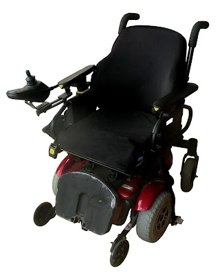 A small electric wheenchair with padded cushions and a roho seat pad.