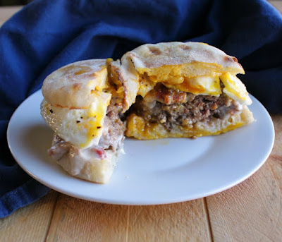 smothered breakfast burger cut in half on plate