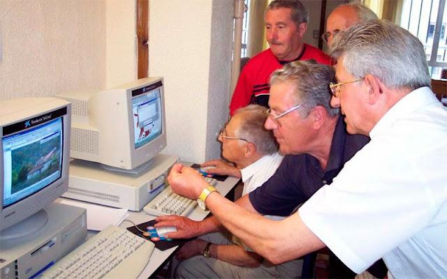 Algunos mayores frente a un ordenador durante un curso , convenio con la Caixa