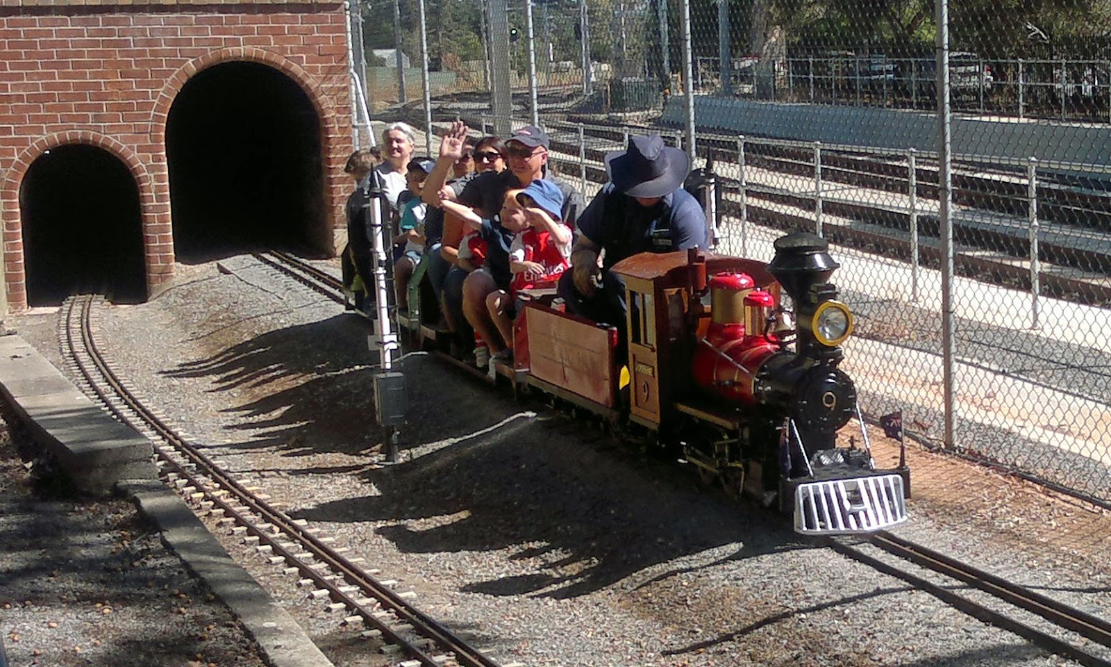 "Model American style steam locomotive coming out of a tunnel. The loco is named ""Yosemite Valley Railroad Jofesine No. 9""  travelling with two carriages loaded with passengers.  The full-scale 'real-life' suburban railway lines can be seen beyond the fence."