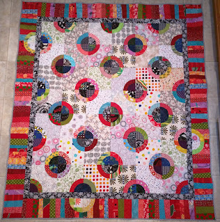 Piano keys border in reds surround polka dot quilt.