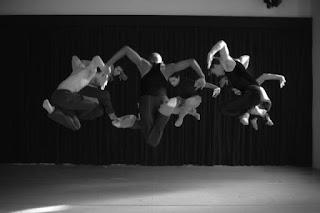 """A fotografia em preto e branco mostra cena da coreografia """"Vadiando""""de Ana Vitória Freire. Seis bailarinos em círculo com os braços abertos em arco, um foco de luz evidencia seus músculos e pernas dobradas que pairam no ar em um salto. Um bailarino está com o dorso desnudo, outros três, com camisetas sem mangas. Eles vestem calças compridas. Ao fundo como cenário, uma cortina."""