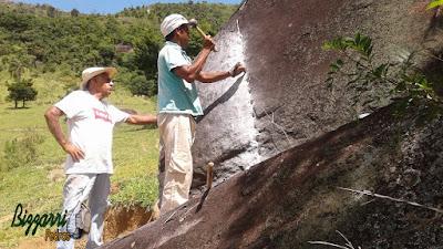 Bizzarri fazendo o que gosta, garimpando pedras na pedreira. Na foto orientando no corte da pedra conforme um projeto para fazer um banco de pedra no jardim, sendo a pedra da foto um granito na cor cinza claro.