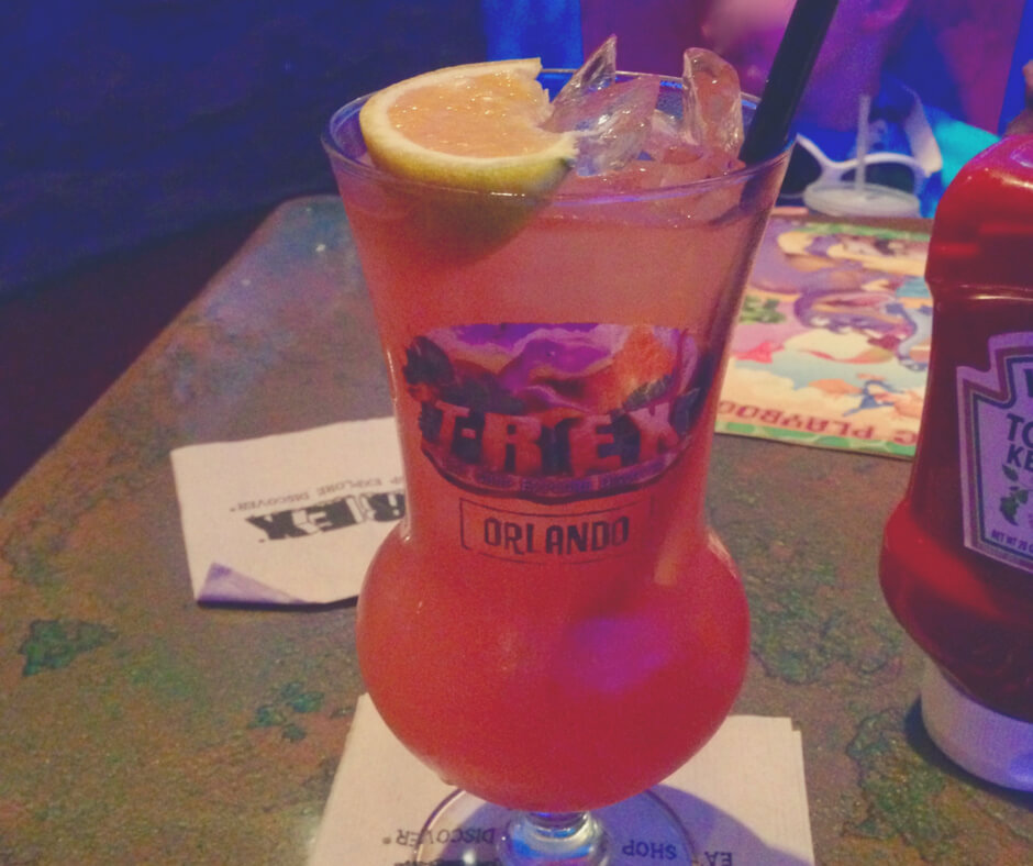 A tropical looking cocktail in a T-Rex glass from T-Rex restaurant in Walt Disney World