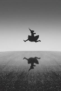perempuan meloncat dengan bayangan di lantai
