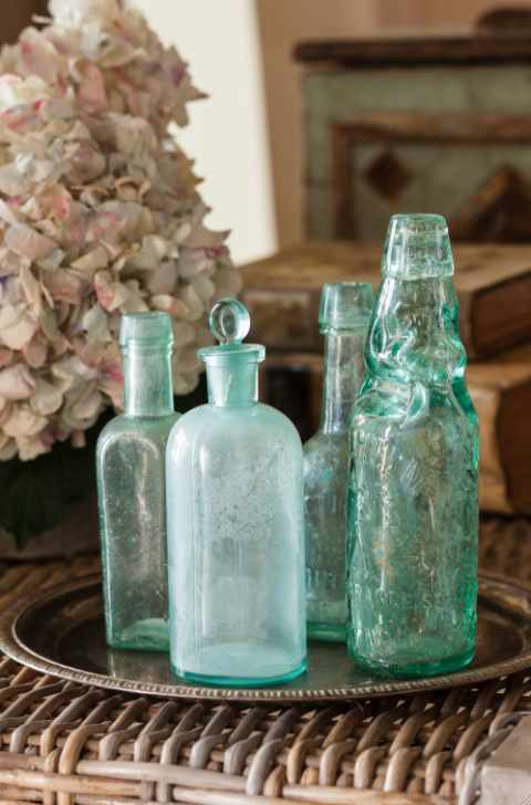 Green vintage bottles on a silver tray. Come see this Rustic Elegant French Gustavian Cottage by Decor de Provence in Utah! #frenchcountry #frenchfarmhouse #interiordesigninspiration #rusticdecor #europeanfarmhouse #housetour
