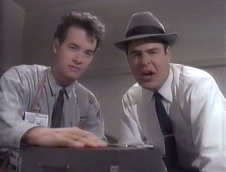 Tom Hanks and Dan Aykroyd as police detectives looking into camera