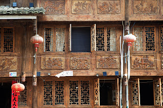 Traditional Chinese building, showcasing an ornately carved facade with lanterns in the windows.