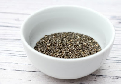 A white bowl full of black chia seeds