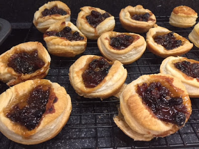 Cooked pastry cases filled with mincemeat on a cooling rack