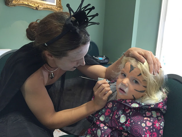 Tin Box Tot having her face painted as a tiger by a witch